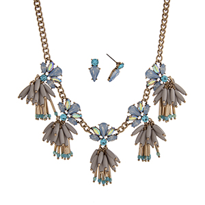 "Burnished gold tone necklace set displaying blue rhinestones with dangling gray beads. Approximately 17"" in length."