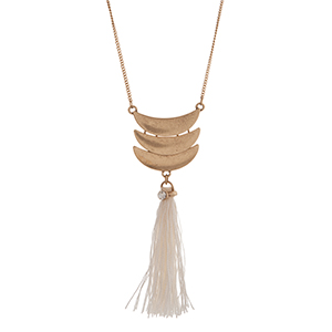 "Worn gold tone necklace displaying three layered crescents with a linked ivory fabric tassel. Approximately 29"" in length."