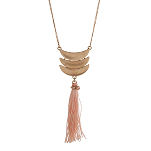 "Worn gold tone necklace displaying three layered crescents with a linked peach fabric tassel. Approximately 29"" in length."