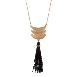 "Worn gold tone necklace displaying three layered crescents with a linked black fabric tassel. Approximately 29"" in length."