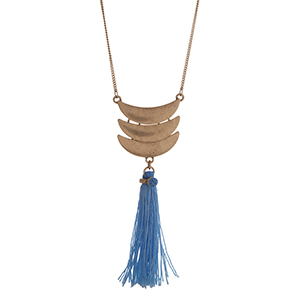 "Worn gold tone necklace displaying three layered crescents with a linked blue fabric tassel. Approximately 29"" in length."