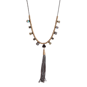 "Gray cord necklace displaying black, gray, and yellow cabochons with a gray leather tassel and gold tone accents. Approximately 30"" in length."