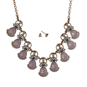"""Worn gold tone necklace set displaying pink opal teardrop shape cabochons surrounded by clear rhinestones. Approximately 16"""" in length."""