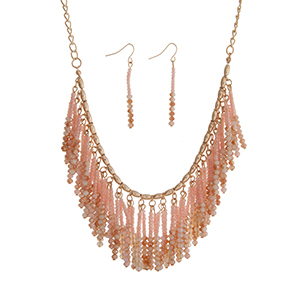"Gold tone necklace set displaying a cluster of pink and peach beaded fringe. Approximately 18"" in length."