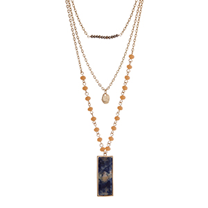 "Gold tone layering necklace displaying gray and peach beads, a hammered disk, and a sodalite natural stone pendant. Approximately 23"" in length."