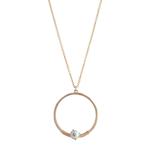 "Gold tone necklace displaying a ring with a wire wrapped iridescent rhinestone. Approximately 29"" in length."