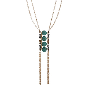 "Gold tone double strand necklace displaying four turquoise beads, black and brown beads, and two chain tassels. Approximately 33"" in length."