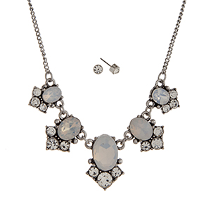 "Burnished silver tone necklace set displaying white oval cabochons with round clear rhinestone accents. Approximately 15"" in length."