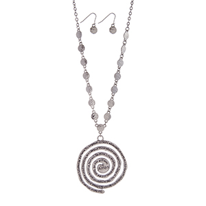 "Silver tone necklace set displaying hammered disk with a spiral pendant stamped with the Lord's Prayer. Approximately 24"" in length."