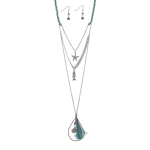 """Silver tone turquoise beaded layering necklace set displaying a chevron pattern with a starfish a fish charm and an open teardrop shape with a fabric tassel and sea life charms. Approximately 31"""" in length."""
