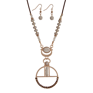 """Brown cord necklace set displaying ivory beads and a round gold tone pendant wrapped with thread. Approximately 28"""" in length."""