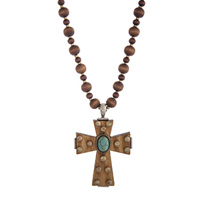 "Dark brown wood and gold tone bead necklace displaying a wood cross with studs and a turquoise stone focal. Approximately 33"" in length."