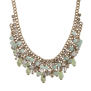 "Burnished gold tone necklace displaying a cluster of mint and green beads and clear rhinestones. Approximately 15"" in length."