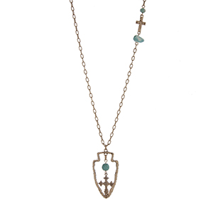 """Burnished gold tone necklace displaying a hammered cross station with a turquoise stone and bead and a wire wrapped arrowhead pendant with a turquoise bead and hanging cross. Approximately 29"""" in length."""