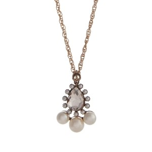 "Gold tone necklace displaying a clear teardrop shape cabochon surrounded by faux ivory pearls. Approximately 28"" in length."