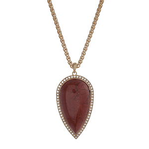 "Gold tone necklace with a 2 1/2"" clay red teardrop shape stone pendant with rhinestone accents. Approximately 32"" in length."