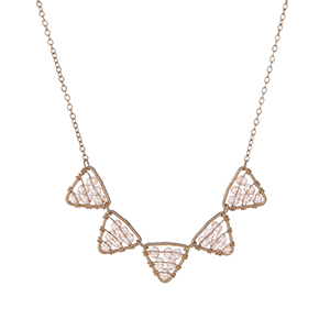 "Dainty gold tone necklace displaying peach beaded triangles. Approximately 16"" in length."