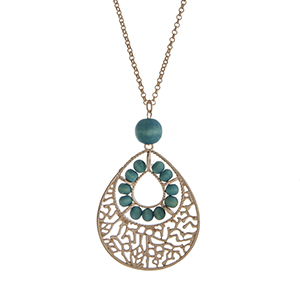 "Gold tone necklace displaying a teardrop shape pendant with turquoise wood bead accents. Approximately 29"" in length."