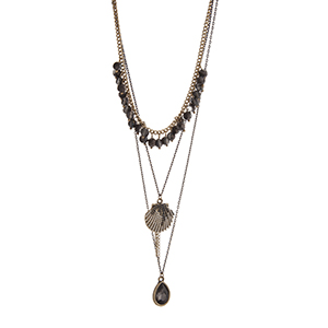 "Gold tone layering necklace displaying black dangling beads, a seashell charm, and a teardrop shape black diamond stone. Approximately 24"" in length."