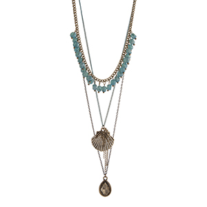 "Gold tone layering necklace displaying turquoise dangling beads, a seashell charm, and a teardrop shape topaz stone. Approximately 24"" in length."