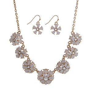 "Gold tone necklace set displaying white layered flowers. Approximately 15"" in length."