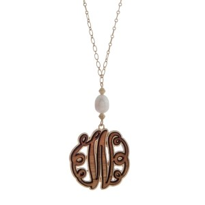 """Worn gold tone necklace with a 1.5"""" wooden 'W' initial and freshwater pearl bead. Approximately 36"""" in length."""