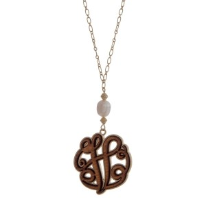 """Worn gold tone necklace with a 1.5"""" wooden 'V' initial and freshwater pearl bead. Approximately 36"""" in length."""