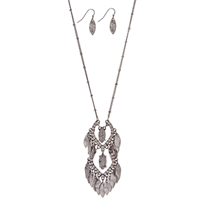 """Silver tone necklace set with a howlite stone pendant accented by white opal rhinestones and metal fringe. Approximately 32"""" in length."""