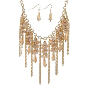 "Gold tone statement necklace set with ivory and champagne beads and metal chain fringe. Approximately 18"" in length."