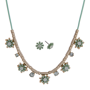 "Mint green cord necklace set with mint green flowers and gold tone beads. Approximately 24"" in length."