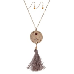 "Gold tone necklace set featuring a pendant with white opal stones and a gray tassel. Approximately 32"" in length."