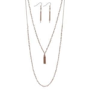 "Dainty gold tone double layer necklace set with ivory beads accented with a chain tassel. Approximately 26"" in length."