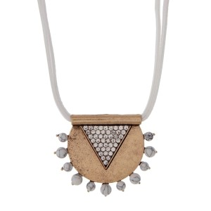 """White leather necklace featuring a burnished gold tone pendant accented with clear rhinestones and howlite stones. Approximately 32"""" in length."""