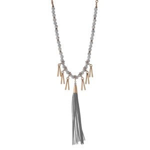 "Burnished gold tone necklace with howlite beads featuring a gray tassel and accented with metal fringe. Approximately 32"" in length."