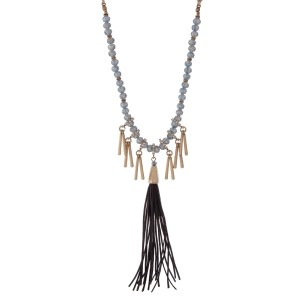 "Burnished gold tone necklace with navy blue beads featuring a gray tassel and accented with metal fringe. Approximately 32"" in length."