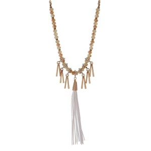"Burnished gold tone necklace with mint green beads featuring a white tassel and accented with metal fringe. Approximately 32"" in length."