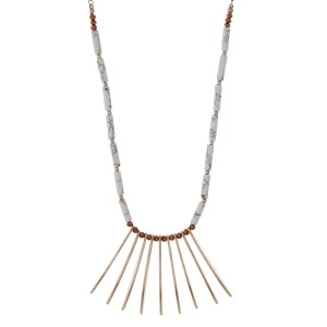 "Gold tone necklace featuring metal fringe, accented with howlite and brown beads. Approximately 32"" in length."