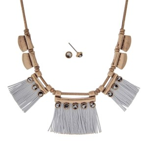 "Burnished gold tone necklace set with white leather fringe and black stones. Approximately 18"" in length."