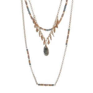 """Gold tone triple layer necklace featuring a natural stone pendant accented with champagne and green beads. Approximately 28"""" in length."""