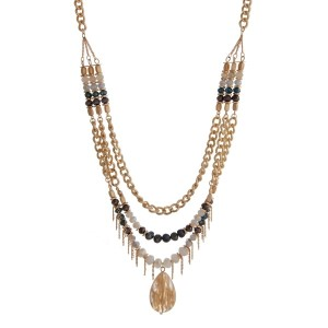 "Gold tone triple layer necklace with teal, white and gray faceted beads and a natural stone pendant. Approximately 28"" in length."