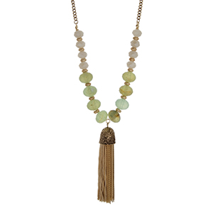 "Gold tone necklace set with mint green natural stone beads, ivory glass beads, and a beige fabric tassel. Approximately 32"" in length."