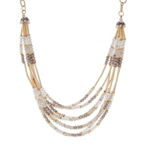 "Gold tone necklace featuring multiple rows of white and gray beads with gold hardware. Approximately 16"" in length."
