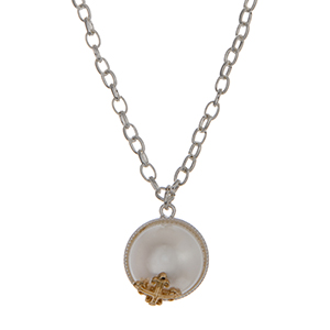 "Silver tone necklace set with a white pearl pendant accented with a gold tone cross. Approximately 16"" in length."