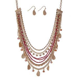 "Burnished gold tone necklace set with strands of pink beads, clear rhinestones, and metal fringe. Approximately 18"" in length."