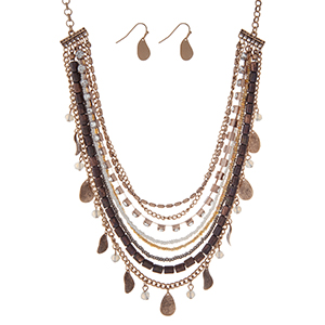 "Burnished gold tone necklace set with strands of neutral beads, clear rhinestones, and metal fringe. Approximately 18"" in length."