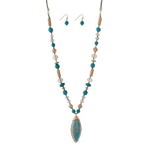 "Gray cord necklace set with turquosie and gold tone beads with an oval pendant. Approximately 32"" in length."