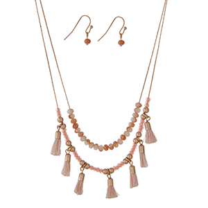 "Dainty gold tone double layer necklace set with peach beads and small blue tassels. Approximately 18"" in length."