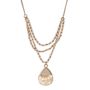 """Gold tone necklace with ivory beads and a beige natural stone pendant. Approximately 30"""" in length."""