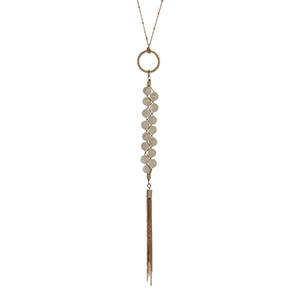 "Gold tone necklace with a braided ivory beaded pendant and a chain tassel. Approximately 36"" in length."