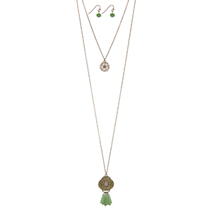 "Gold tone double layer necklace set with a filigree circle pendant and a mint green beaded Marrakesh pendant. Approximately 34"" in length."